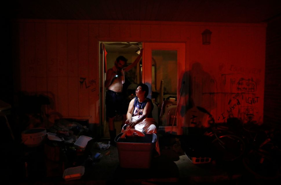 Tasha Hughes, bathes her daughter, Madison, 4, as Jeffrey Dumich holds a flashlight outside their room at the damaged America
