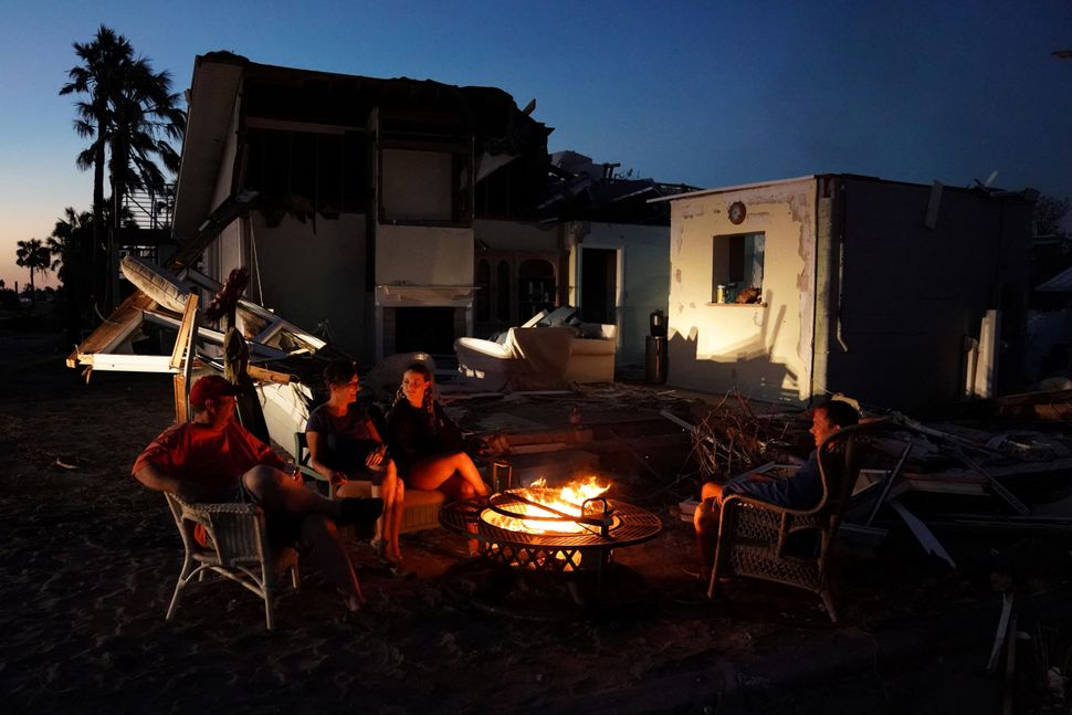 A family sits by a fire and prepares to eat a dinner of MREs in front of their house with no roof in Mexico Beach.
