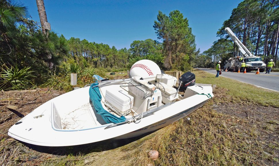 A motorboat and a large decorative baseball sit on the side of U.S Highway 98 in the aftermath of Hurricane Michael in St. Ja