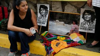 Laura Zuniga Caceres, daughter of Honduran indigenous and environmental rights activist Berta Caceres, sits outside the court where eight men accused in her mother's murder were to be tried in Tegucigalpa, Honduras, Monday, Oct. 15, 2018. The trial was once again suspended on Monday at the request of Caceres' family members, who fear the trial will not be conducted fairly.(AP Photo/Fernando Antonio)