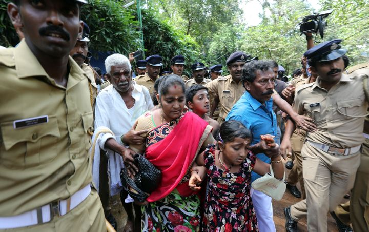 Police escort a woman and her family after she was harassed by protesters while seeking the entry to the Lord Ayyappa Temple