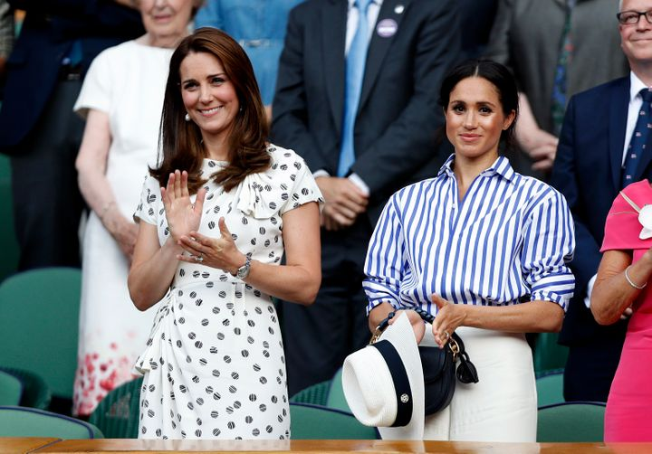 The Duchess of Cambridge and the Duchess of Sussex applaud in the royal box after the Wimbledon Championships ladies' singles final on July 14, 2018.