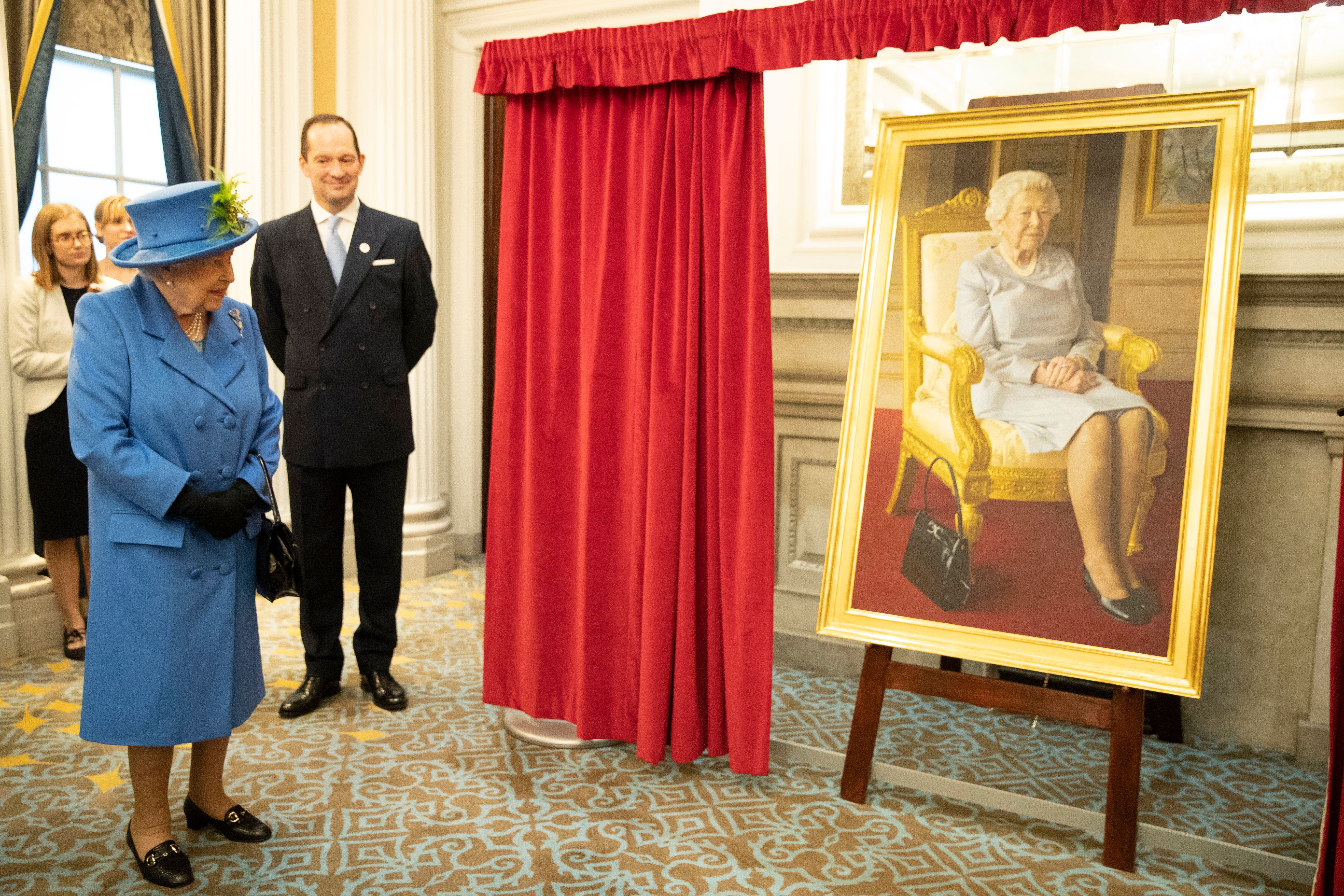 LONDON, ENGLAND - OCTOBER 17: Queen Elizabeth II views a new portrait depicting Her Majesty painted by BP Portrait Award 2017 winner, Benjamin Sullivan, the portrait commissioned to celebrate 100 years of the RAF Club during the opening of the new wing and unveiling of a series of newly-commissioned artworks as she visits the RAF Club to mark its centenary year on October 17, 2018 in London, England. (Photo by Heathcliff O'Malley - WPA Pool/Getty Images)
