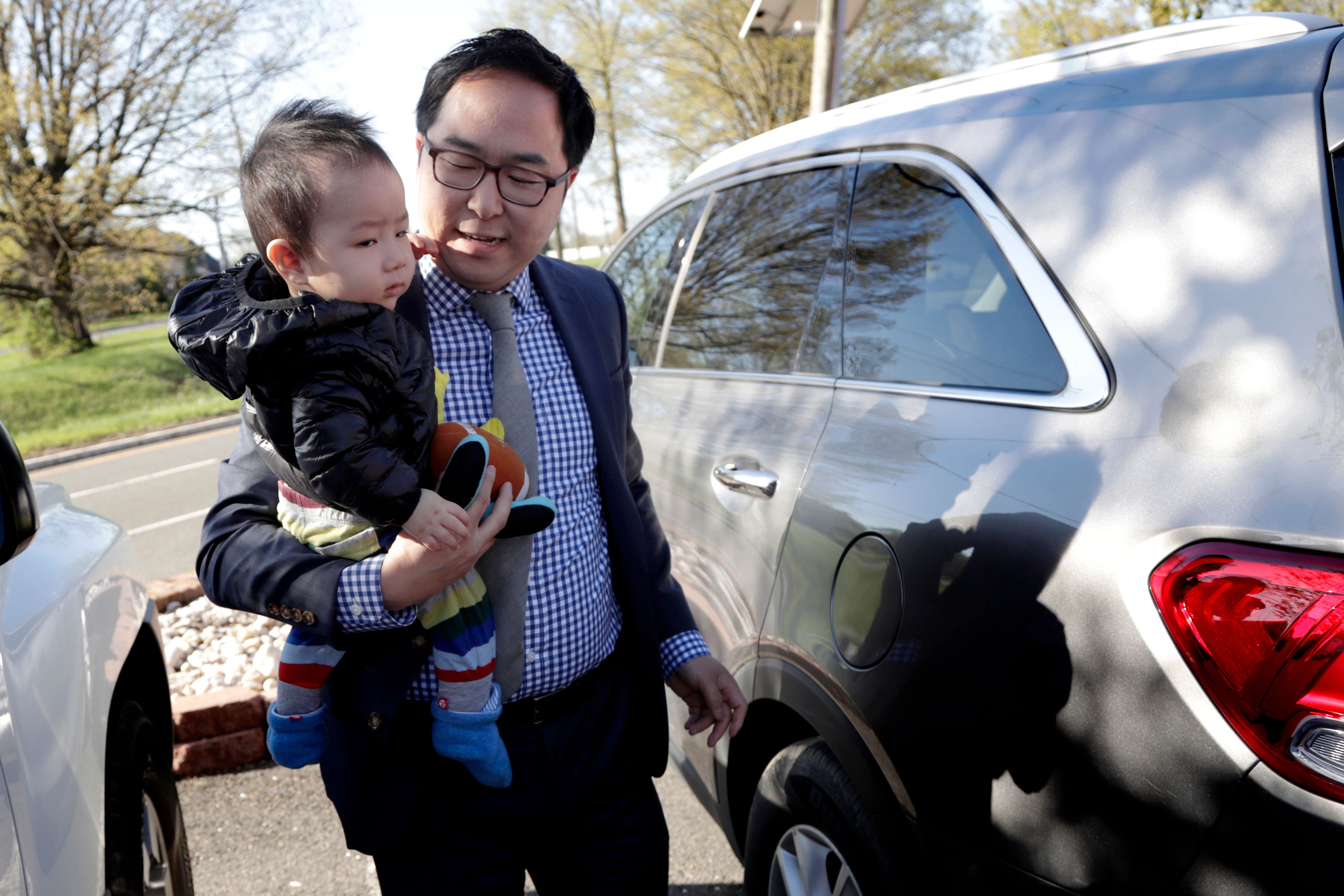 In a photo taken Tuesday, May 1, 2018, Andy Kim carries his 9-month-old son, August Kim, on his first day of school in Bordentown, N.J. Kim, who grew up in Marlton, N.J., is running for U.S. Congress. (AP Photo/Julio Cortez)