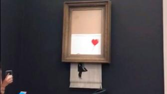 "FILE - In this file image taken from video on Friday, Oct. 5, 2018, people watch as the spray-painted canvas ""Girl with Balloon"" by artist Banksy is shredded at Sotheby's, in London. Sotheby's says the winning bidder for a Banksy painting that self-destructed during an auction last week has decided to go through with the purchase. The auction house says a female European collector was the successful bidder who offered 1.04 million pounds for ""Girl With Balloon."" Just after the hammer came down, the bottom half of the work passed through a shredder concealed in the frame. Sotheby's said Thursday, Oct. 11 the painting is being sold with a new title, ""Love is in the Bin."" (Pierre Koukjian via AP)"