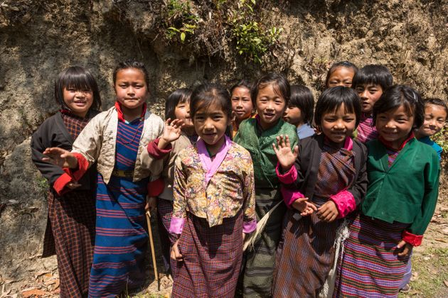 Young schoolgirls in traditional dress pose for their picture by the road in Talo,