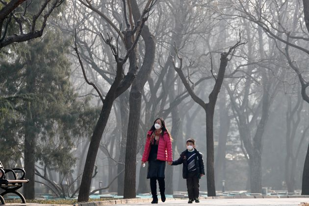 A woman and a child wearing masks to protect against pollution in Ritan Park, Beijing. Despite it's huge...