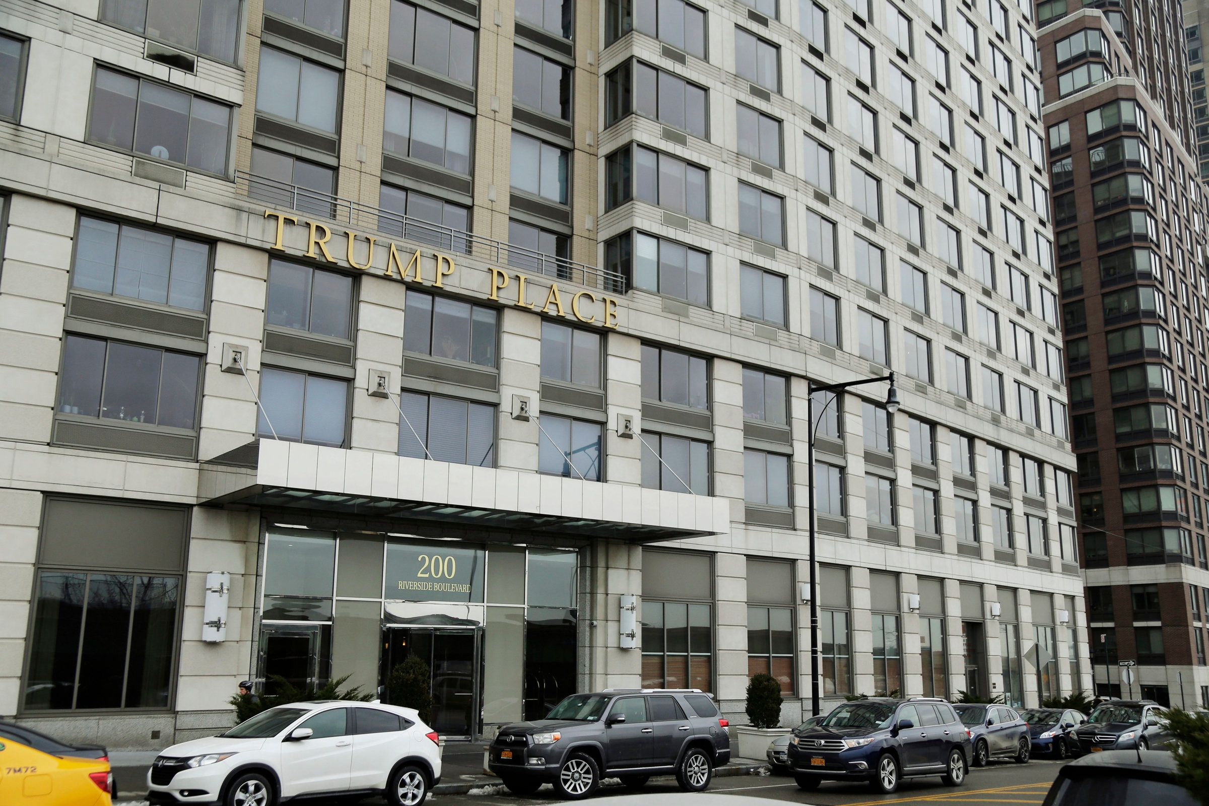 """<p> FILE - In this Jan. 11, 2018 file photo, vehicles line the curb outside of """"Trump Place,"""" at 200 Riverside Boulevard in New York. A New York state judge ruled Thursday May 3, 2018, that condominium owners in the high-rise can stop displaying the name licensed from President Donald Trump nearly two decades ago. The ruling doesn't order the brassy letters removed from the tower overlooking the Hudson River. Rather, the decision clears the way for owners to vote on the issue. (AP Photo/Seth Wenig, File)"""