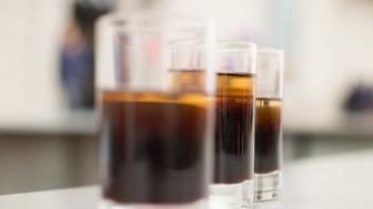 three glass of refreshment of cola on table
