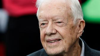 FILE - In this Oct. 23, 2016, file photo, former President Jimmy Carter sits on the Atlanta Falcons bench before the first half of an NFL football game between the Atlanta Falcons and the San Diego Chargers, in Atlanta.  Carter has been treated for dehydration while volunteering with Habitat for Humanity in Winnipeg. (AP Photo/John Bazemore, File)
