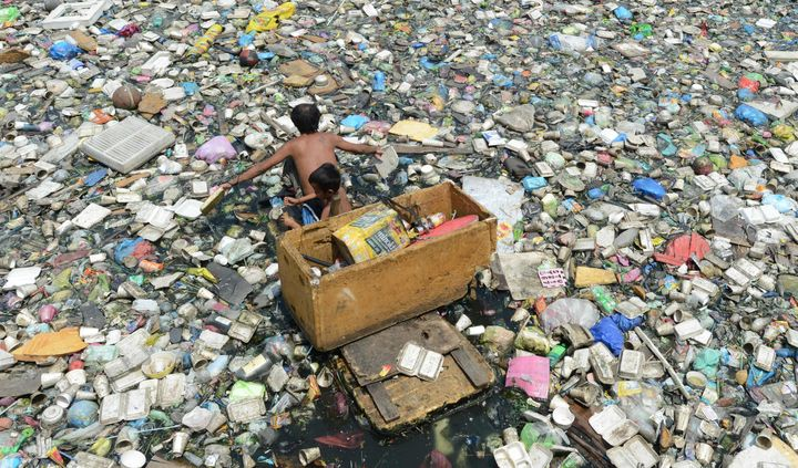 A father and son paddle through a garbage-filled river as they collect plastic bottles to sell in junk shops in Manila, Phili