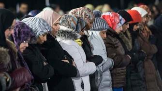 A group of women pray during the funeral service for three of the six victims of the Quebec City mosque shooting at the Maurice Richard Arena Thursday, February 2, 2017 in Montreal. THE CANADIAN PRESS/Paul Chiasson