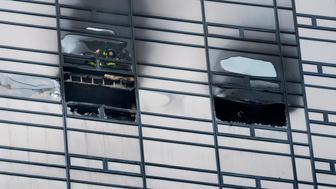 Firefighters look out from the window of a fire damaged apartment in Trump Tower in New York on  Saturday, April 7, 2018. The Fire Department says the blaze broke out on the 50th floor shortly before 6 p.m. Saturday. (AP Photo/Craig Ruttle)
