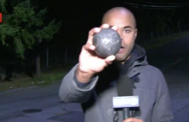 KIRO TV journalist Michael Spears shows one of the two-pound metal balls that fell out of a truck in Seattle on Thursday.