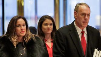 FILE- In this Dec. 12, 2016, file photo, then-Rep. Ryan Zinke, right, R-Mont., who was then=President-elect Donald Trump's choice for interior secretary, arrives at Trump Tower, in New York with his wife Lola Zinke, left, and aide Heather Swift. U.S. Capitol Police have charged Wilfred M. Stark, 49, of Falls Church, Va, with simple assault following a confrontation with Swift, a spokeswoman for Zinke, outside a congressional hearing.  (AP Photo/Richard Drew, File)