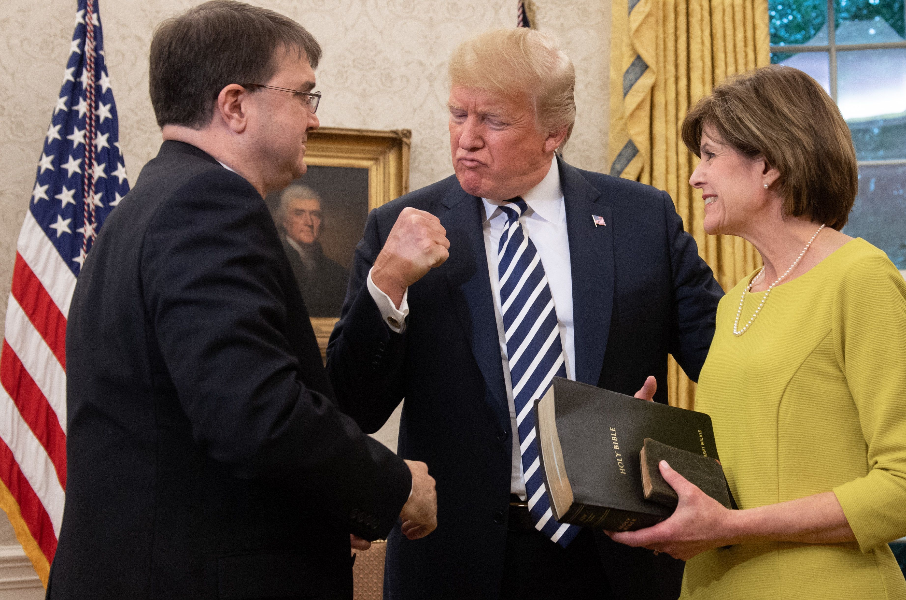 US President Donald Trump pumps his fist alongside Robert Wilkie (L) after he was sworn-in as Secretary of Veterans Affairs, alongside his wife Julia (R), in the Oval Office of the White House in Washington, DC, July 30, 2018. (Photo by SAUL LOEB / AFP)        (Photo credit should read SAUL LOEB/AFP/Getty Images)