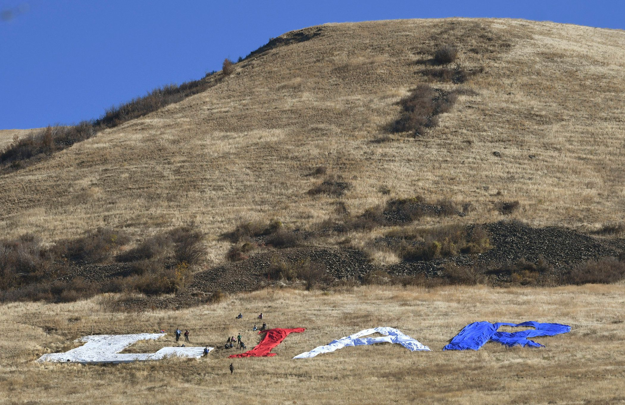 Protesters hiked up Mount Jumbo Thursday morning, Oct. 18, 2018 in Missoula, Mont., to lay out letters spelling the word LIAR in protest of President Donald Trump's visit. Using the permanent letter L on Mount Jumbo, protesters spread large pieces of fabric to complete the word LIAR.  President Trump is visiting Missoula to campaign for Republican Matt Rosendale, who is challenging Democratic U.S. Sen. Jon Tester.  (Kurt Wilson/The Missoulian via AP)