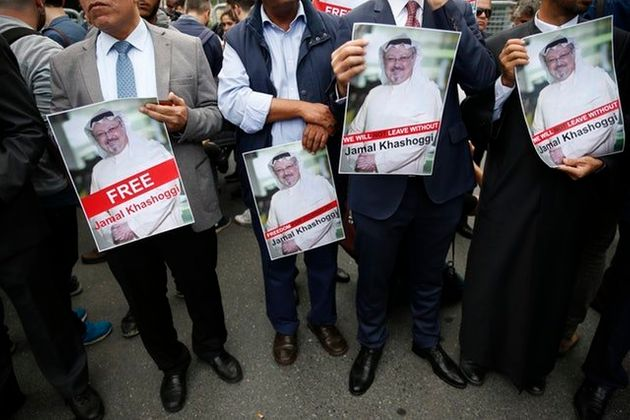 Members of the Turkish-Arab journalist association hold posters with photos of the missing Saudi