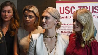 A group of current and former USC students who are survivors of alleged sexual assault by gynecologist Dr. George Tyndall from the USC student health center and which occured over a 30 years period, support each other during a press conference in Los Angeles, California on October 18, 2018. - Nearly 20 survivors of Dr. Tyndall called upon members of the USC Board of Trustees to speak out on behalf of survivors and also to ask Attorney General Xavier Becerra to launch an independent investigation of the USC administration. (Photo by Mark RALSTON / AFP)        (Photo credit should read MARK RALSTON/AFP/Getty Images)