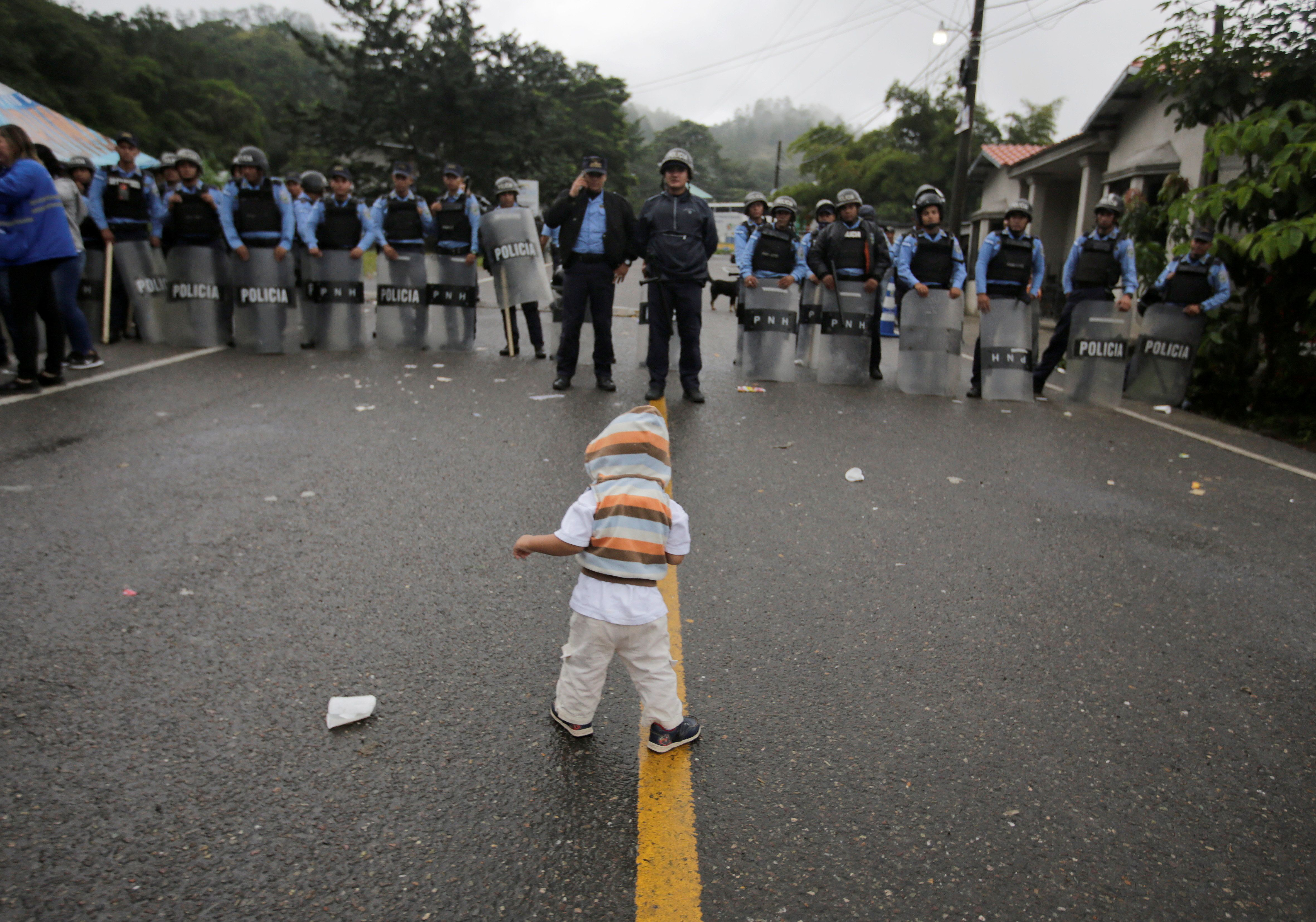 REFILE - CORRECTING DESCRIPTION OF SCENE A Honduran child, traveling with a caravan of Honduran migrants trying to reach the U.S., stands in front of Honduran police officers blocking the street, in Agua Caliente, Honduras October 17, 2018. REUTERS/Jorge Cabrera