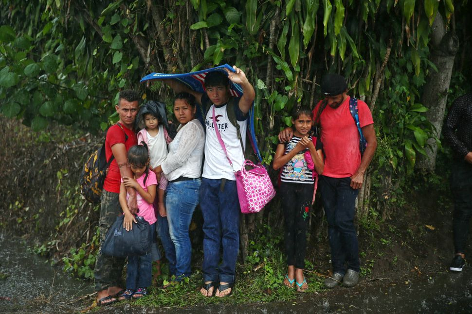 Migrant children take shelter from rain.