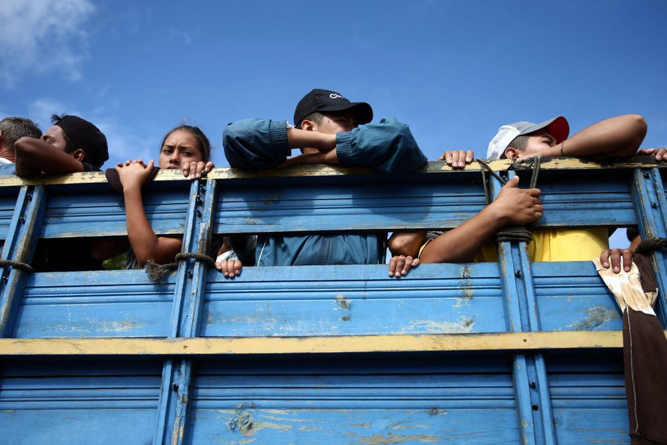 Another truck packed with people weaves through Central America.