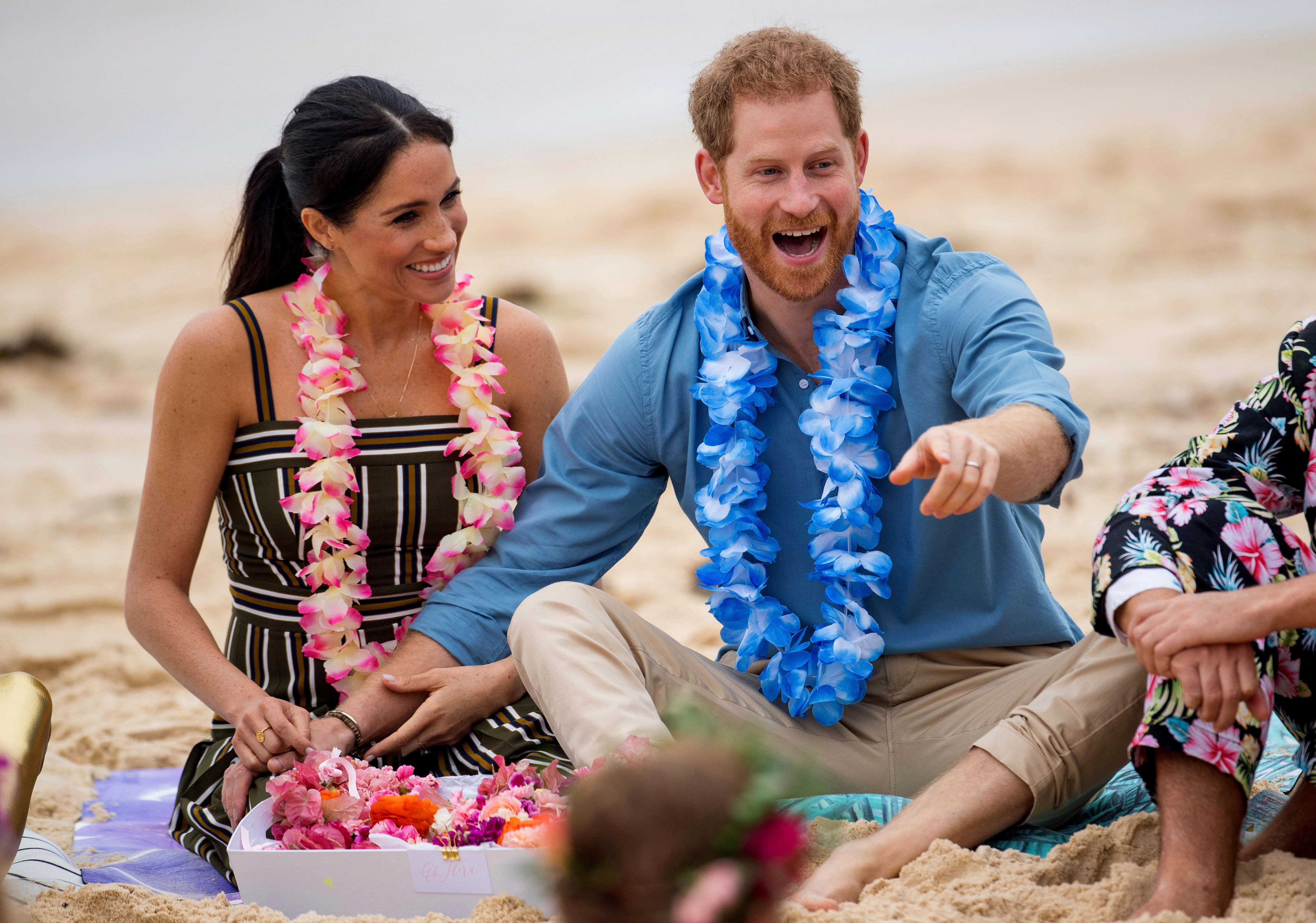 Britain's Prince Harry and Meghan, Duchess of Sussex meet with a local surfing community group, known as OneWave, raising awareness for mental health and wellbeing in a fun and engaging way at Bondi Beach in Sydney, Australia, Friday, Oct. 19, 2018. . Prince Harry and his wife Meghan are on day four of their 16-day tour of Australia and the South Pacific. (Dominic Lipinski/Pool via AP)