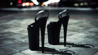 Women's high-heeled shoes. Shoes for strip standing on the cobblestones at night in the city. Extremely high heeled fetish shoes