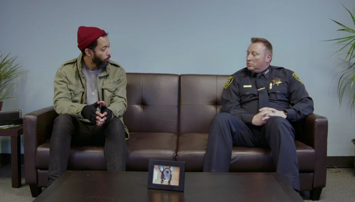 "Cenac sits with a police chief from Elgin, Illinois, in Season One of ""Problem Areas"" on HBO."