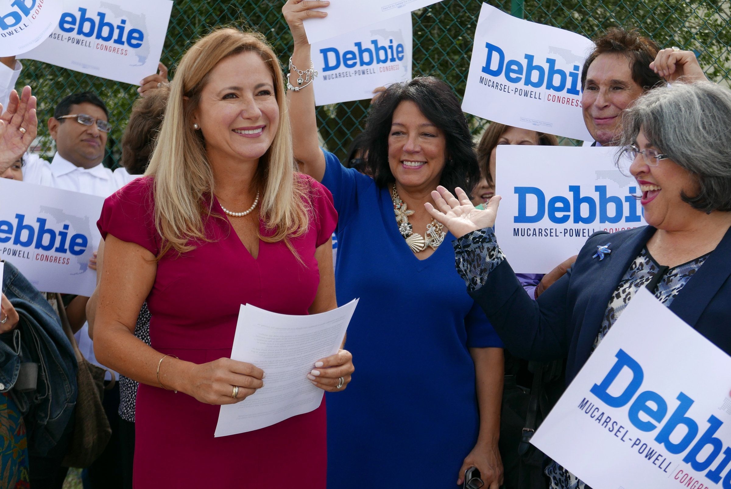 Surrounded by a small group of family and supporters, Democrat Debbie Mucarsel-Powell, left, announces she is running against Republican U.S. Rep. Carlos Curbelo, outside the West Perrine Health Center in Miami on August 2, 2017. (Jose A. Iglesias/El Nuevo Herald/TNS via Getty Images)