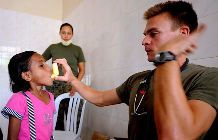 Lt. Brandon Van Noord shows a girl how to use an inhaler at a clinic.