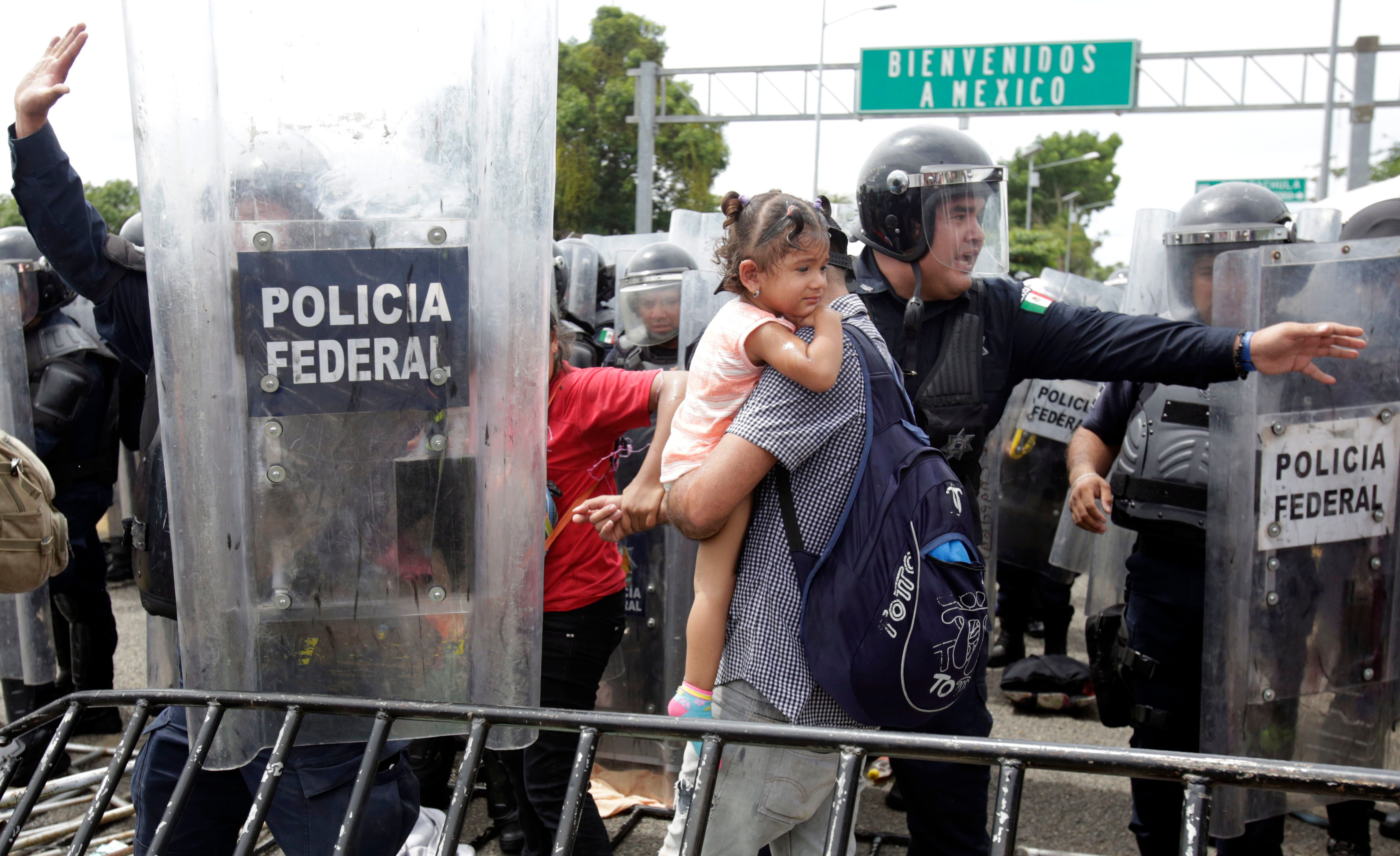 A Honduran migrant family is allowed to pass through to safety by Mexican Federal Police in riot gear, at the border crossing in Ciudad Hidalgo, Mexico, Friday, Oct. 19, 2018. Central Americans traveling in a mass caravan broke through a Guatemalan border fence and streamed by the thousands toward Mexican territory, defying Mexican authorities' entreaties for an orderly migration and U.S. President Donald Trump's threats of retaliation. (AP Photo/Moises Castillo)