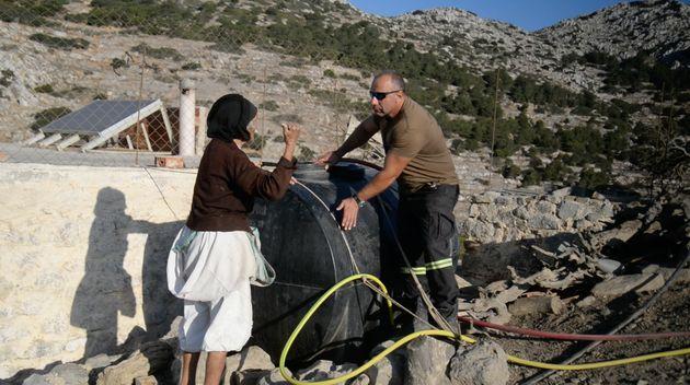 Ο πυροσβέστης Νικόλας Παραγιός γεμίζει το άδειο βυτίο της Αρχοντούλας, της μοναδικής κατοίκου στην περιοχή...