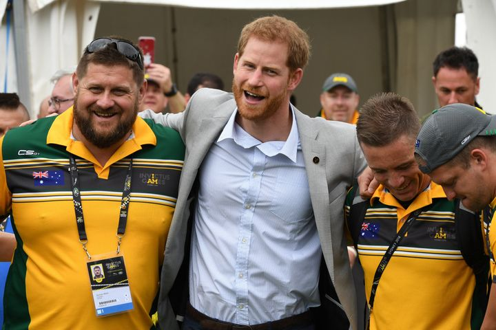 Prince Harry embraces participants in the Invictus Games Sunday morning as wife Meghan Markle took a break.