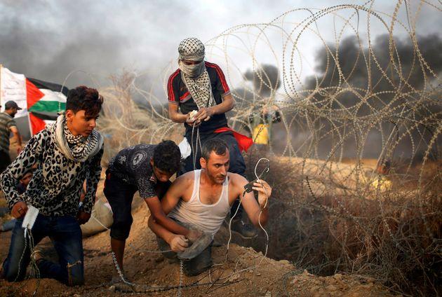Un Palestinien handicapé se prépare pour lancer des pierres sur les soldats israéliens,...