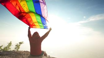 man in red hoodie waving rainbow LGBT symbol flag on mountain top bright sunny blue sky background