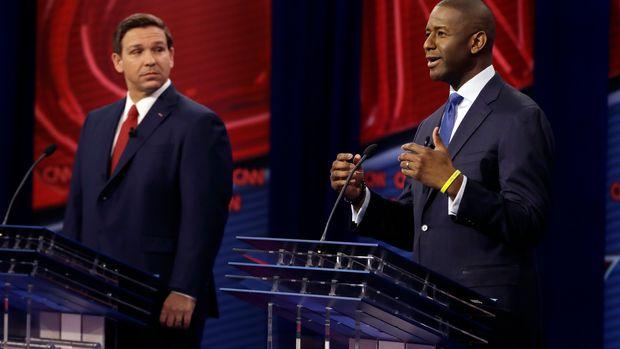 Florida Democratic gubernatorial candidate Andrew Gillum, right, speaks as Republican gubernatorial candidate Ron DeSantis looks on during a CNN debate, Sunday, Oct. 21, 2018, in Tampa, Fla. (AP Photo/Chris O'Meara)