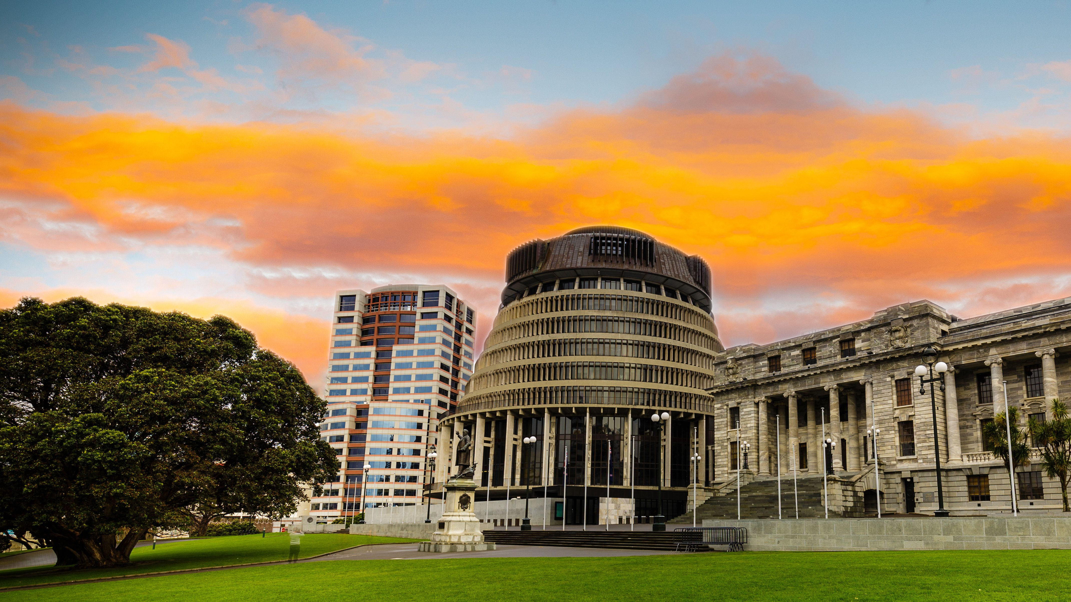 New Zealand parliament building the beehive under a vibrant orange sunset.