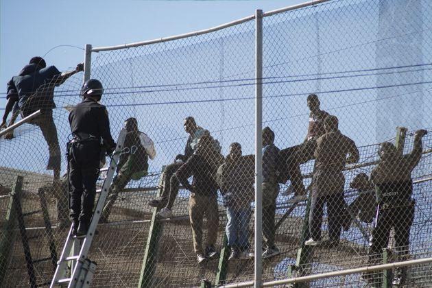 Des migrants escaladent la clôture entre le Maroc et l'enclave espagnole de Melilla,