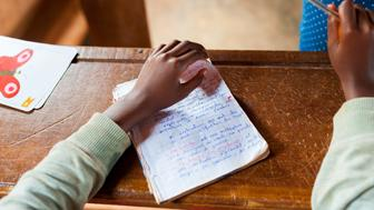 close up of little hand of african child at school with pen writing and learning on desk