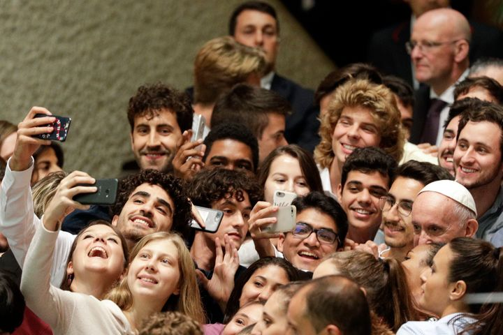 Pope Francis, right, poses with youths attending the Synod at the end of his meeting in the Paul VI hall at the Vatican, Saturday, Oct. 6, 2018.