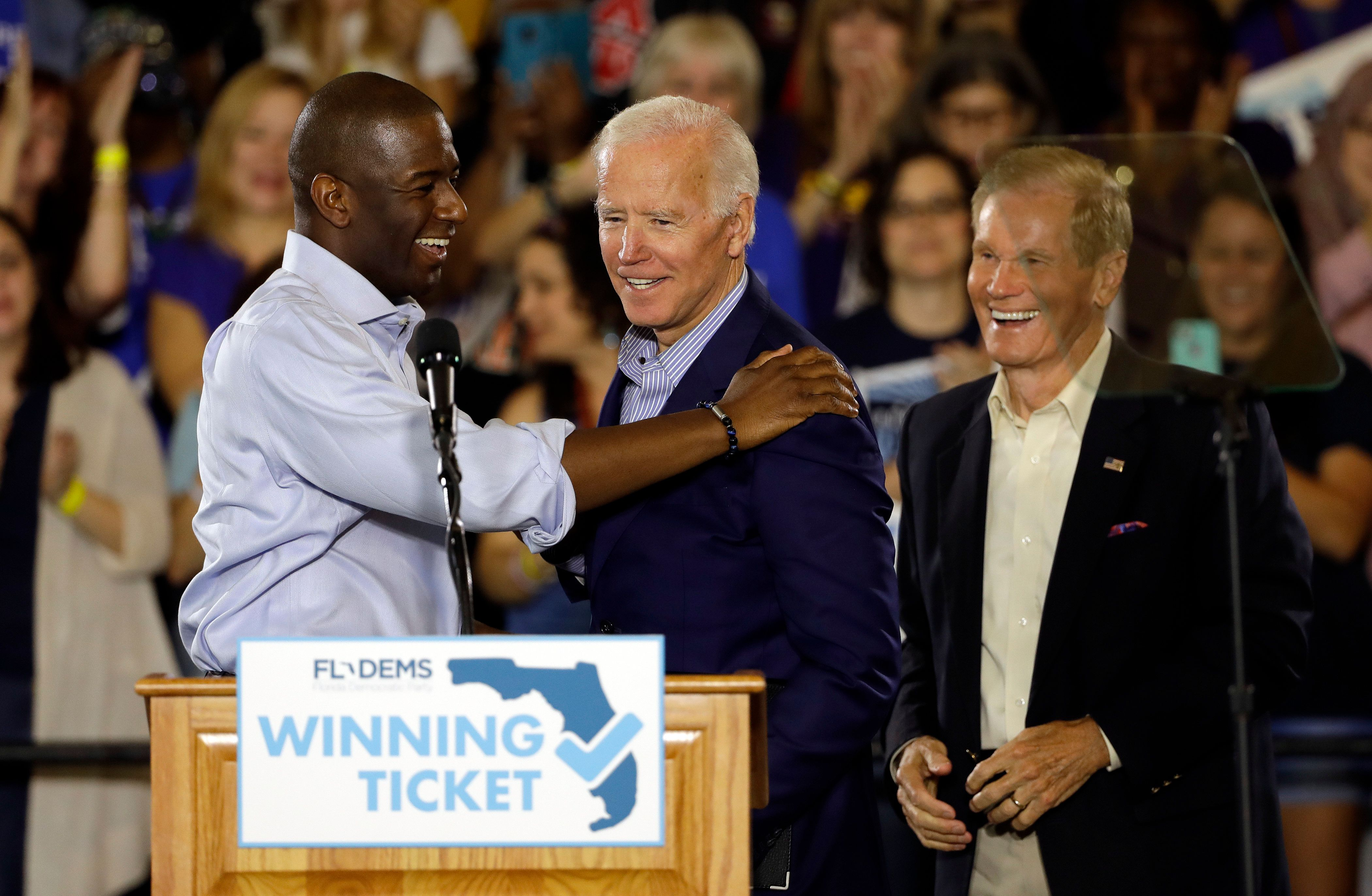 Former Vice President Joe Biden, center, meets Florida Democratic gubernatorial candidate Andrew Gillum, left, and U.S. Sen. Bill Nelson, D-Fla., during a campaign rally for Gillum and Nelson. Monday, Oct. 22, 2018, at the University of South Florida in Tampa, Fla. (AP Photo/Chris O'Meara)