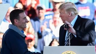 President Donald Trump shakes Nevada Republican governor candidate Adam Laxalt's hand at a campaign rally on Saturday, Oct. 20, 2018 in Elko, Nev. (AP Photo/Alex Goodlett)