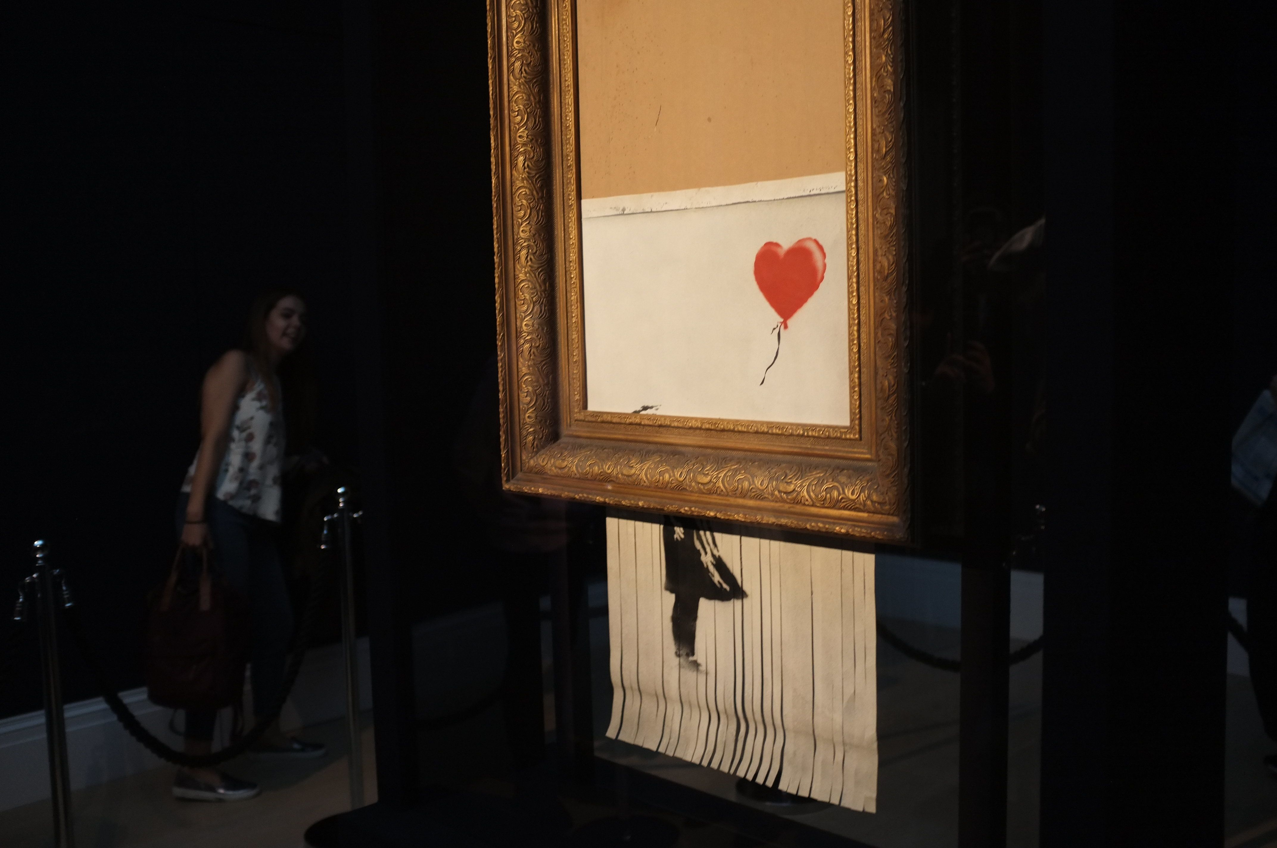 Visitors are pictured as they watch 'Love is in the Bin' by British artist Banksy at Sotheby's auction house, London on October 14, 2018. During Sotheby's Contemporary Art Sale on 5th October the Banksy artwork 'Girl with Balloon' shredded through the bottom of the frame as it was sold. With Banksy being responsible for the shredding, the buyer has agreed to proceed with the sale and it is now titled 'Love is in the Bin' and said to be worth more than the £1.04million paid. (Photo by Alberto Pezzali/NurPhoto via Getty Images)