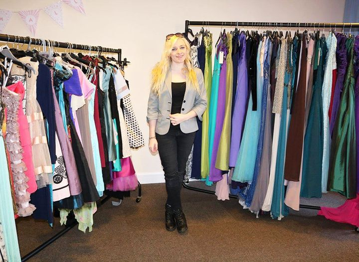 Ally surrounded by prom dresses.