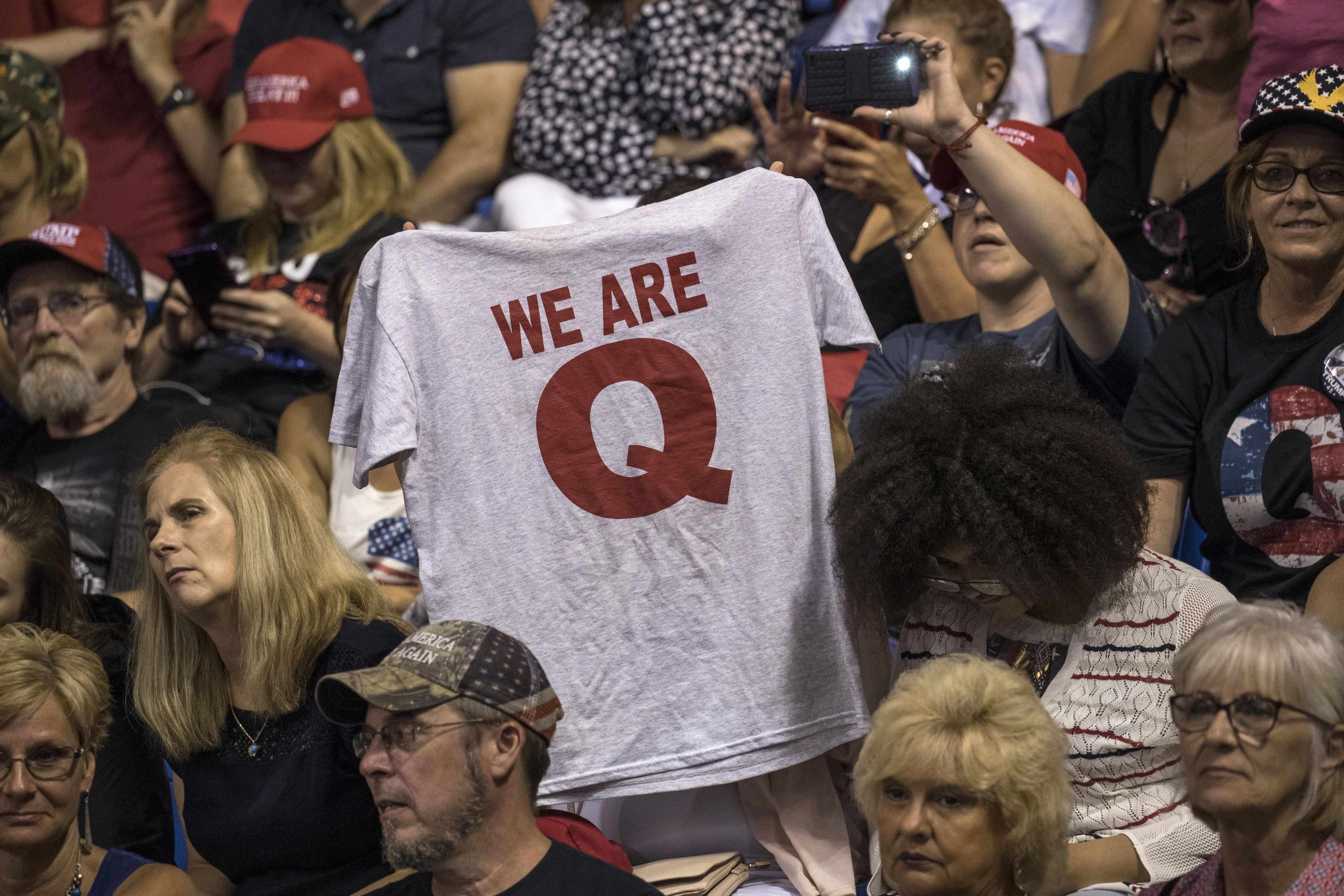 An attendee raises up a T-shirt with the words 'We Are Q' before the start of a rally with U.S. President Donald Trump in Wilkes-Barre, Pennsylvania, U.S., on Thursday, Aug. 2, 2018. Trump tweeted Thursday that Pennsylvania has to love him because he's 'bringing STEEL BACK in a VERY BIG way.' Photographer: Victor J. Blue/Bloomberg via Getty Images