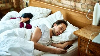 Mature man sending text message as his girlfriend sleeps in the bed, serious expression on face