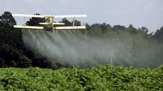 FILE - In this Aug. 4, 2009, file photo, a crop duster sprays a field of crops just outside Headland, Ala. The House passed a Republican-backed measure reversing an Environmental Protection Agency requirement that those spraying pesticides on or near rivers and lakes file for a permit. The chamber voted largely along party lines on May 24, 2017, to approve the Reducing Regulatory Burdens Act. The bill's sponsors say the rule requiring a permit under the Clean Water Act before spraying pesticides is burdensome and duplicative. EPA already regulates pesticide safety under a different law. (AP Photo/Dave Martin, File)