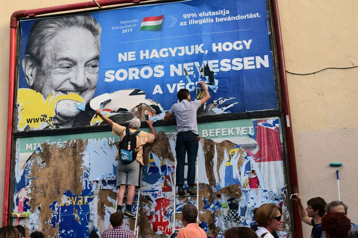 In this July 2017 photo, activists of the Egyutt (Together) party tear down an ad by the Hungarian government against Soros i