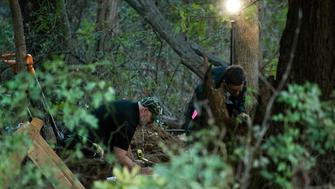 In this Monday, Oct. 22, 2018 photo, detectives investigate the scene where remains believed to be those of a southwestern Michigan woman who disappeared in 2010 were found, in Fulton, Mich. Doug Stewart, who was convicted of killing his estranged wife in 2011, took police to the burial site Monday. (Daniel Vasta /Kalamazoo Gazette via AP)